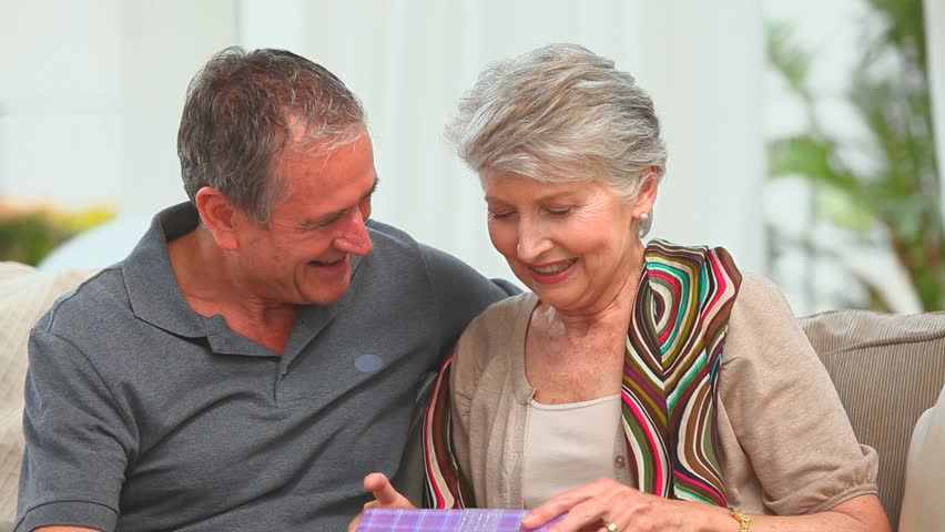 Middle aged couple with a gift looking at the camera in the living room - HD stock video clip