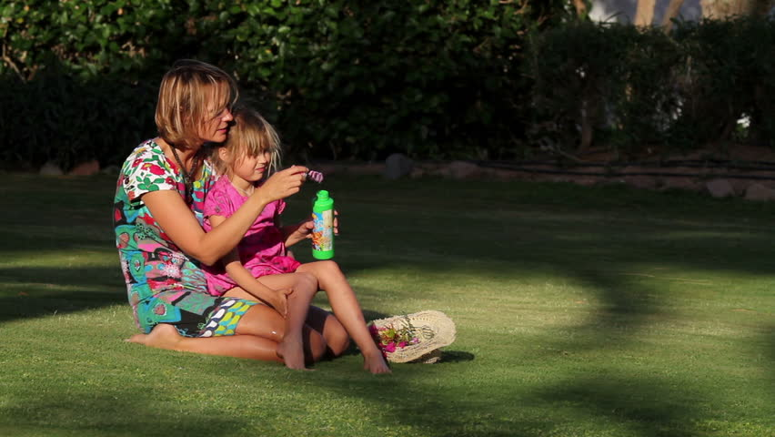 girl with her  mother on the lawn blow bubbles  - HD stock footage clip