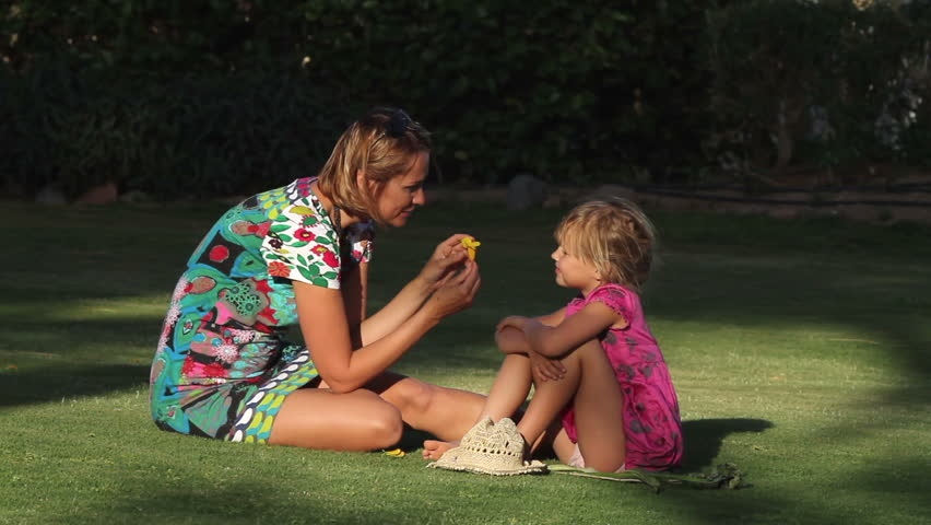 Mother and daughter sit on the grass talking about flowers  - HD stock footage clip