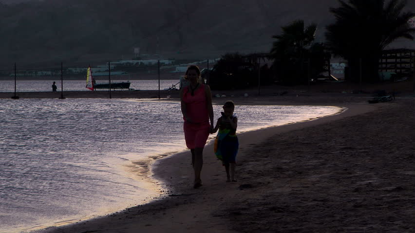 girl with her mother walking on the beach at sunset - HD stock footage clip