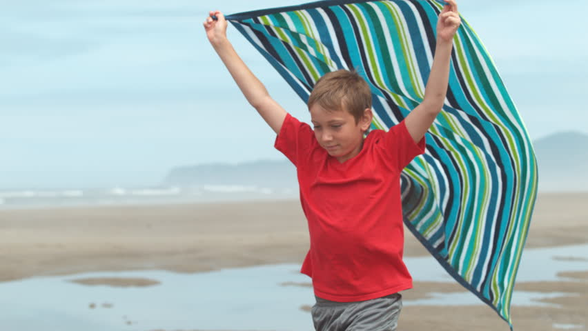 Boy running with towel at beach, slow motion