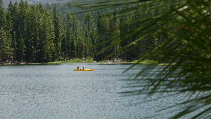 Lassen Volcanic National Park, California, United States of America – July, 2015: A family (father, mother, and child) paddle a kayak on Manzanita Lake.