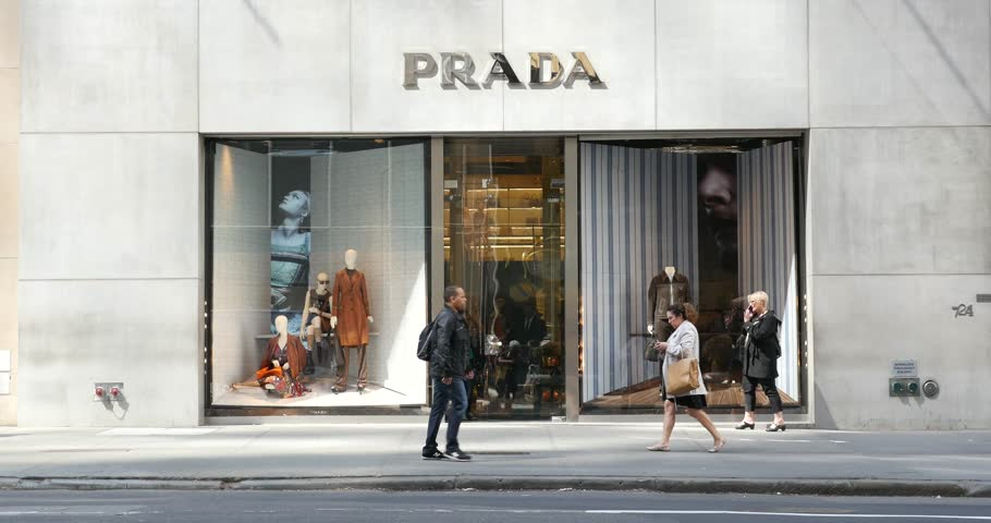 NEW YORK CITY -  MAY 14, 2015: People and traffic in front of Prada store on 5th avenue. The Italian fashion company is present in 65 countries with 250 single brand shops. It was founded in 1913.