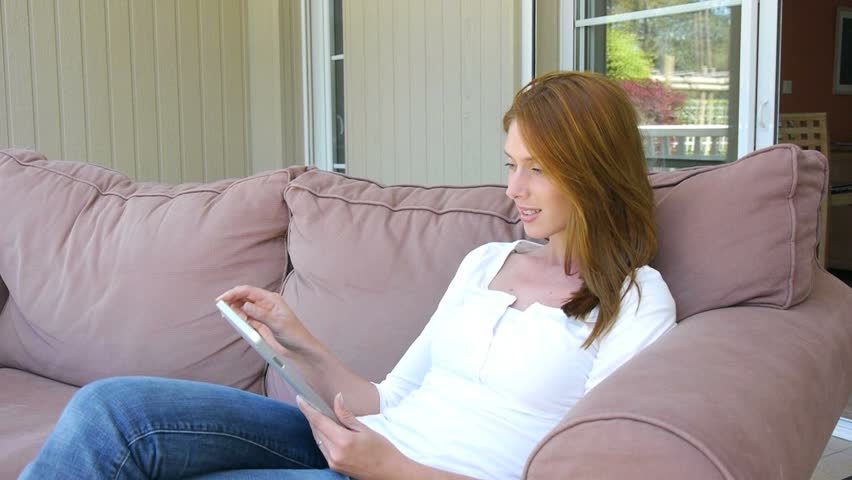 Young woman sitting in couch with electronic tablet - HD stock footage clip