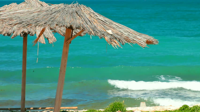 Wooden umbrella on empty beach - HD stock video clip