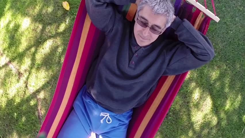 Funny Caucasian middle-aged man relaxing in hammock. Aerial view.