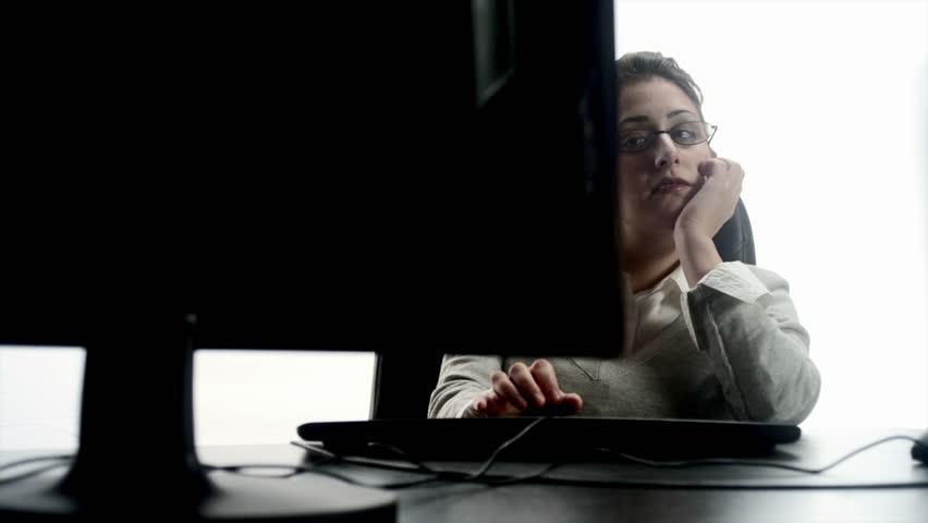 An Hispanic woman falling asleep at a desktop computer  - HD stock video clip
