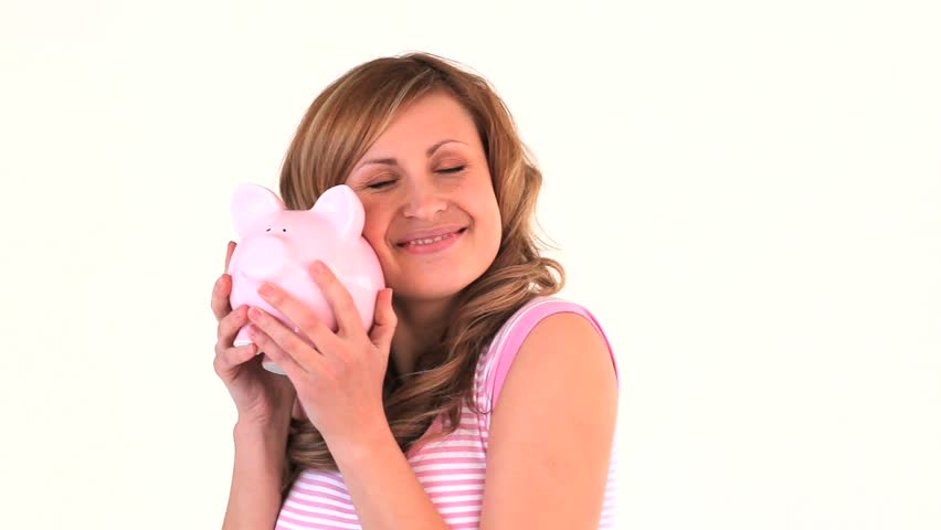 Cute woman posing with a piggy bank in a studio - HD stock footage clip