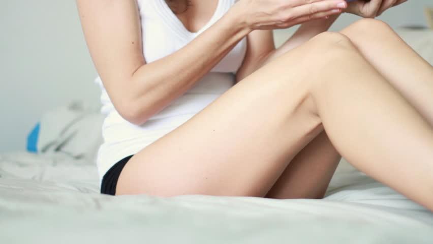 Woman applying moisturizer cream on her leg - HD stock video clip