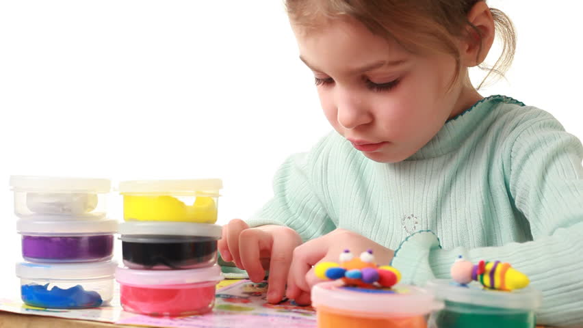 cute little girl rolls on table small black stick from bright colored plasticine - HD stock footage clip