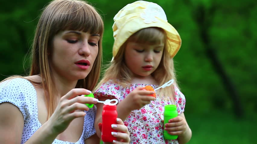 Mother and daughter with soap bubbles. Mother kissing baby  - HD stock video clip