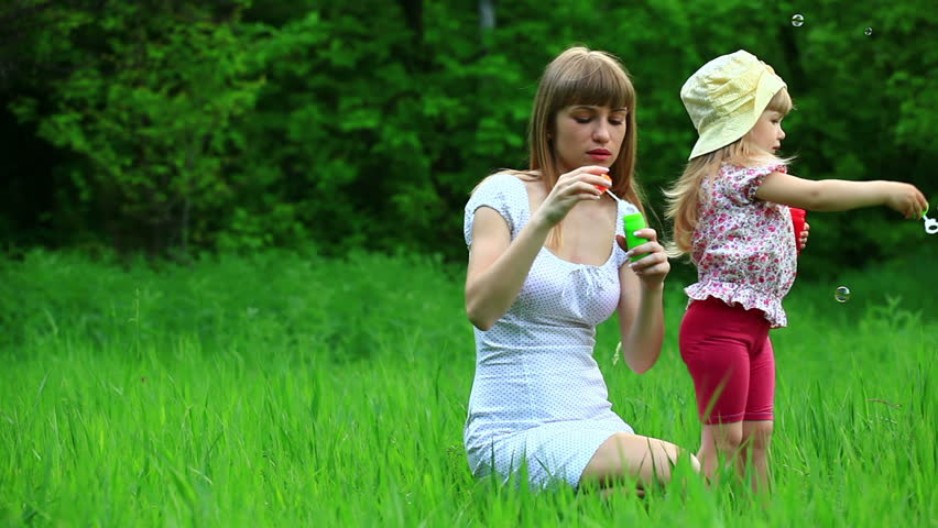 Mother and daughter blowing air bubbles. Tripod.  - HD stock footage clip