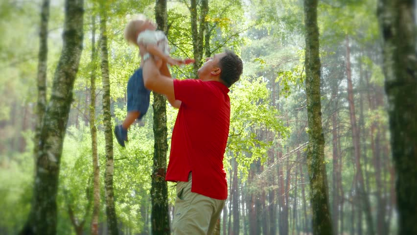 Male, father entertain of  baby boy , throwing up in his arms.  Childhood memories and dreams, happy childhood, happy joy family,baby. Forest Ecology and environment, fresh air - 4K stock footage clip