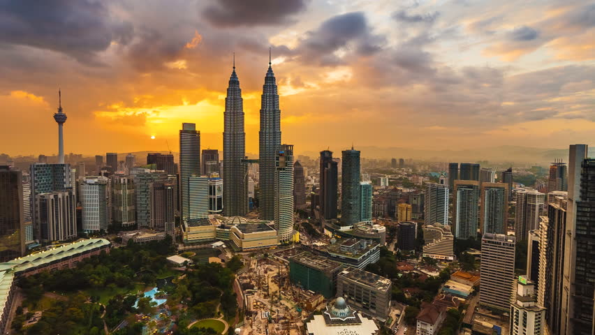 Time lapse: Beautiful and dramatic sunset view of the Kuala Lumpur skyline overlooking the national landmarks,  the Petronas Towers and Kuala Lumpur Tower. - 4K stock video clip