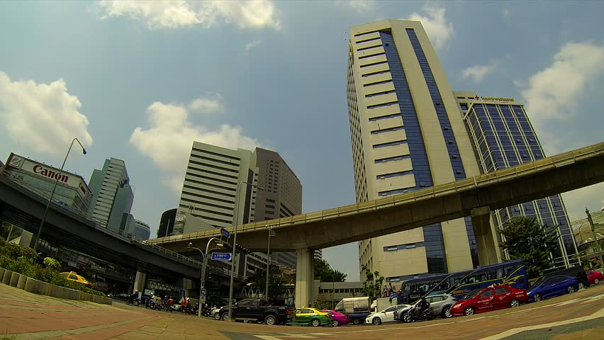 BANGKOK - March 2015: Bangkok's traffic with BTS sky trains passing by. Silom.  - HD stock video clip