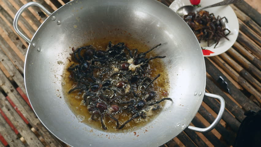 Woman pouring fried oil into a wok with deep-frying tarantulas (upper view), southeast asia , cambodia