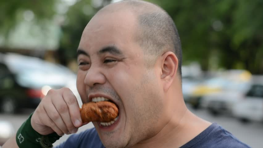 Fat Asian bald head Thai man is biting and eating fried chicken drumstick greedily with hunger with water sweat on his face in 1920x1080 HD quality. He might suffocate because of his gluttony.