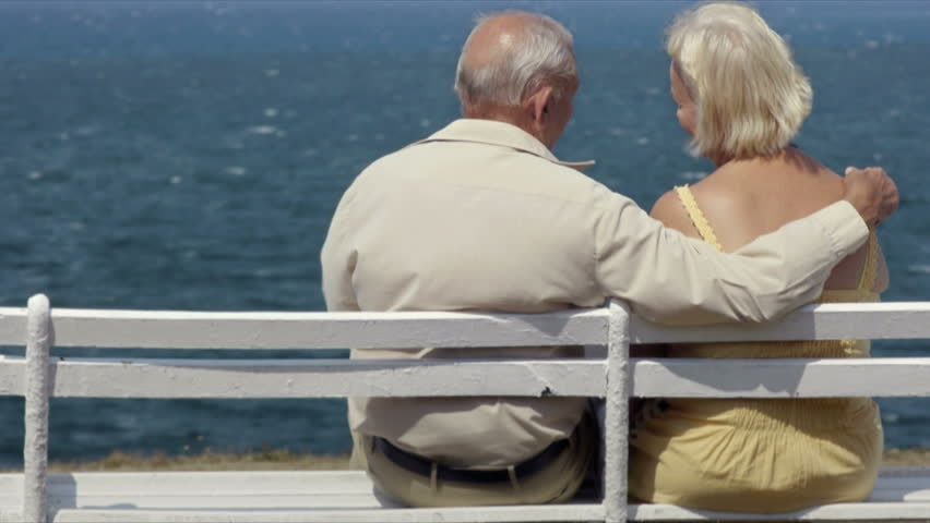 Old people in love, elderly man and woman, husband and wife hugging, senior caucasian couple sitting and relaxing on bench near the sea