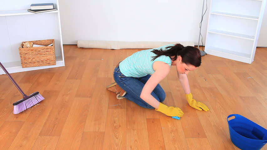 Young woman cleaning the floor of the living-room - HD stock video clip