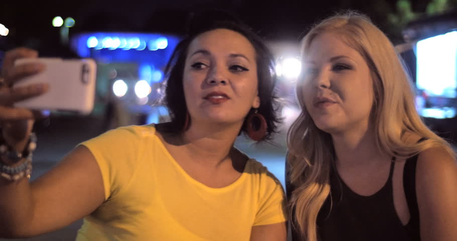 4K Two happy girl female friends look at smartphone then take a selfie self portrait photo after a fun night out in an urban city outdoor neighborhood setting.