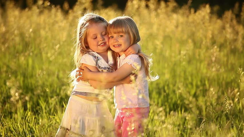 Two sisters embrace. Look at camera. They play in the meadow.