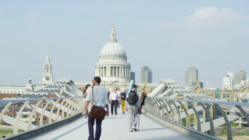 LONDON SEPTEMBER 2014 - Crowd of people crossing the Millennium footbridge.  The bridge was originally nicknamed the wobbly bridge due to it's swaying motion. LONDON, UK 11 SEPTEMBER 2014 EDITORIAL - 4K stock footage clip