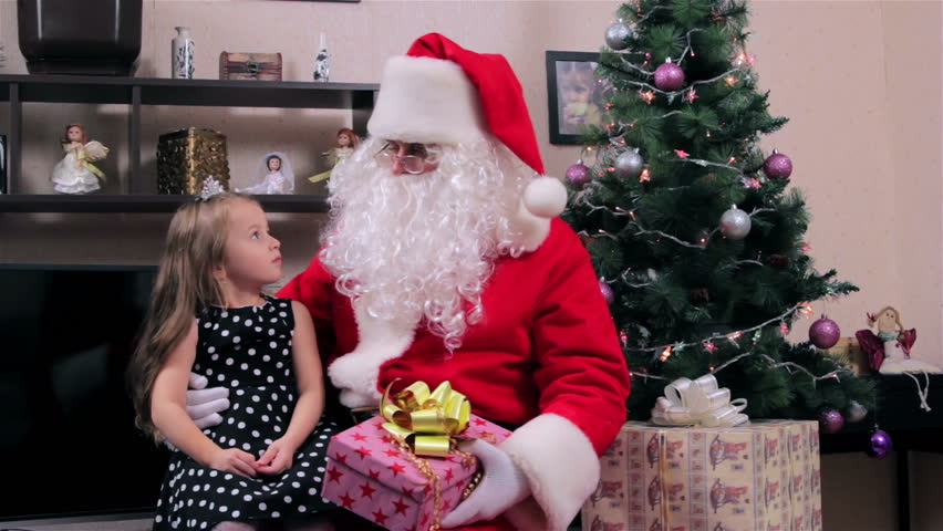 Santa and little girl. Santa hands Teddy bear toy a little girl