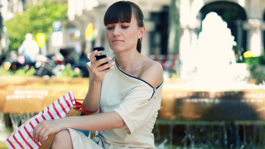 Attractive woman sitting by the fountain and sending sms, slow motion  - HD stock video clip