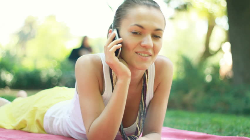 Attractive woman lying in the park and talking on cellphone  - HD stock video clip