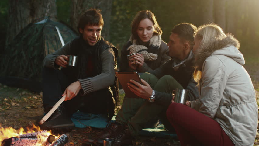 Group of men and women sit next to a campfire with drinks and use tablet in a forest. Shot on RED Cinema Camera in 4K (UHD). - 4K stock video clip