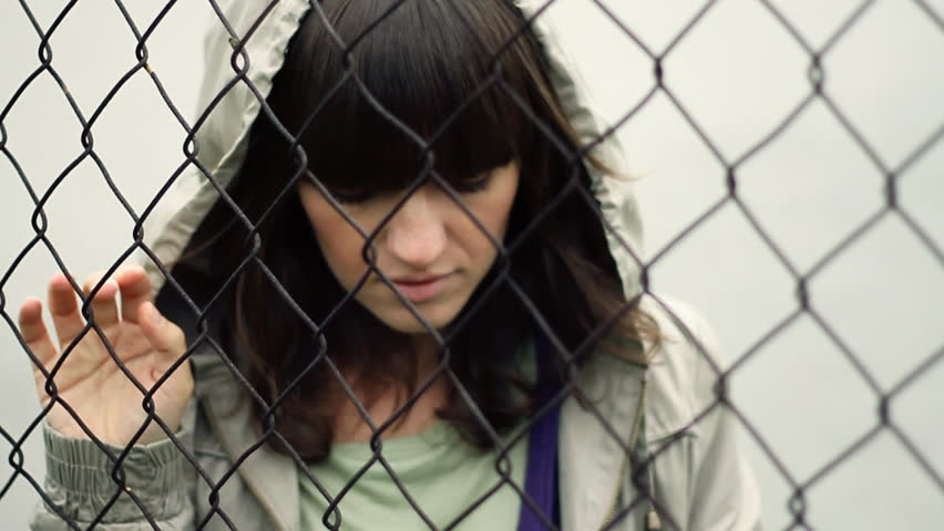Sad woman behind chain-link fence, outdoors, slow motion  - HD stock video clip