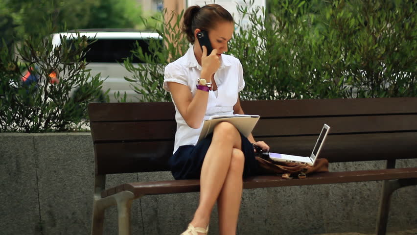 Businesswoman with mobile phone, laptop and documents in the city  - HD stock video clip