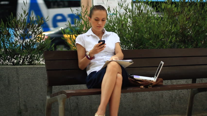 Businesswoman with mobile phone, laptop and documents in the city - HD stock footage clip