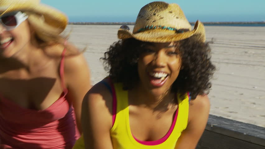 Two women friends at the beach in cowboy hats - HD stock footage clip