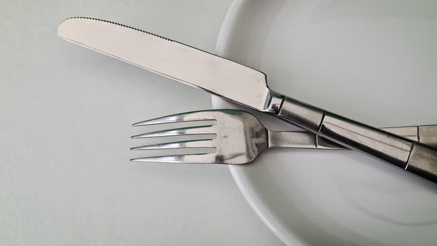 Cutlery close up HD stock footage. Close up sliding shot of a white dining plate with a knife and fork laid on the top. Negative space for title overlays.