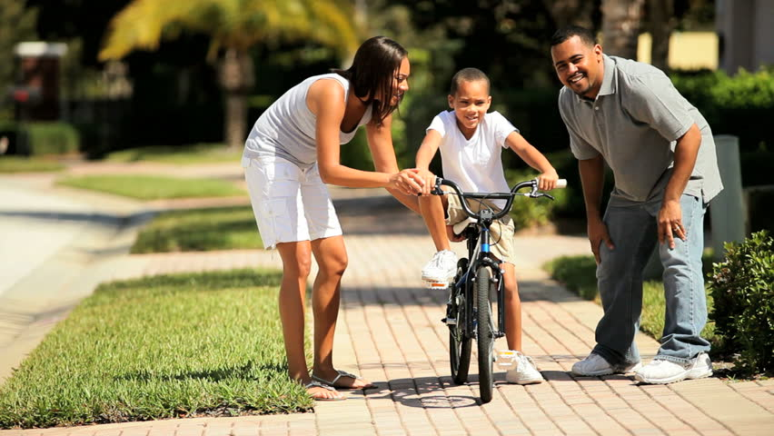 Loving african-american parents teaching their young son to ride a bicycle - HD stock video clip
