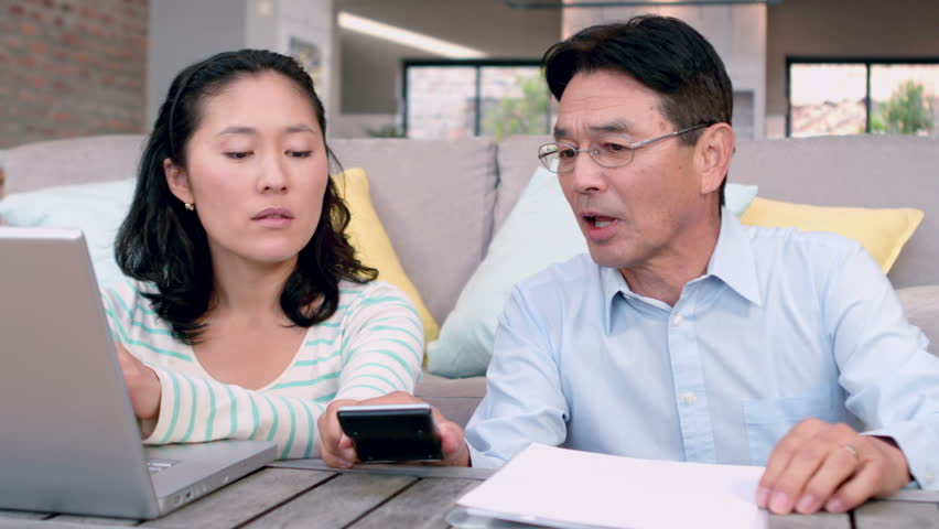 Concetrated couple calculating bills with laptop in living room - HD stock footage clip