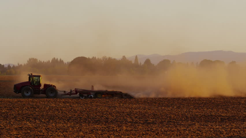 Cinemagraph - Tractor plowing field at sunset. Motion Photo.