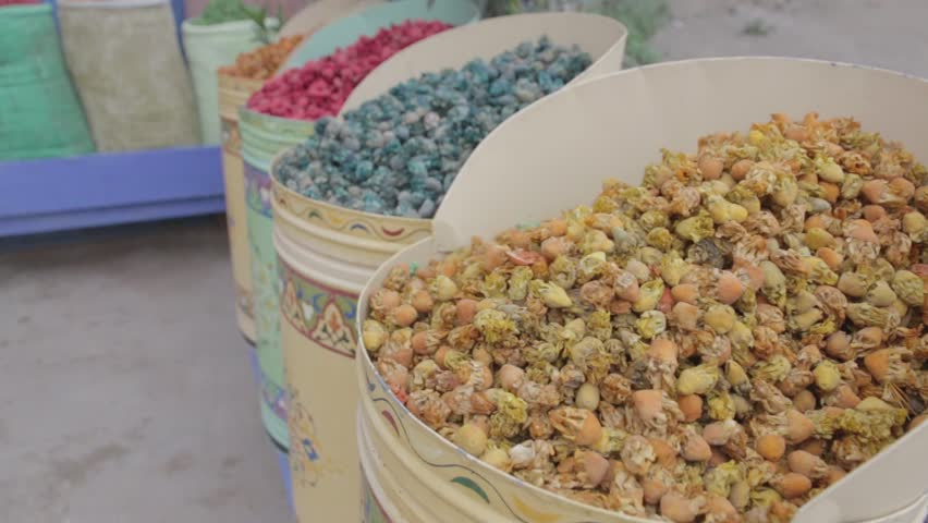 This shot is a panning shot around some vibrant, brightly coloured grain type seed pods. They are stored in beautifully decorated containers and shows off the beautiful culture of Morocco