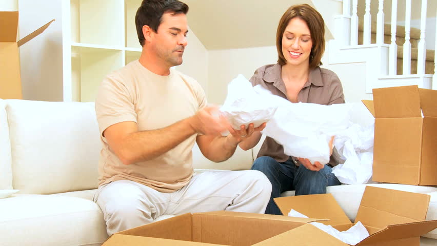 Young caucasian couple unwrapping their possessions following house move - HD stock footage clip