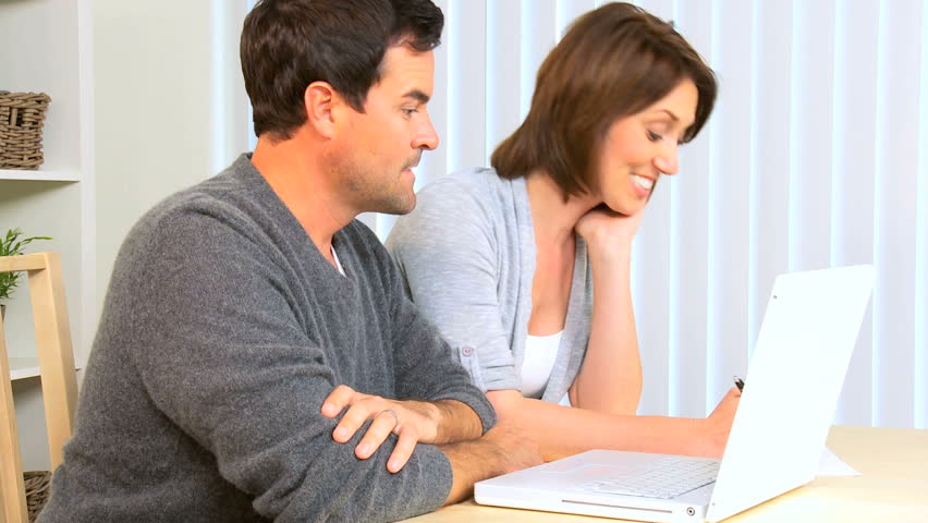 Young caucasian couple at home with laptop computer pleased with the results of their financial planning  - HD stock footage clip