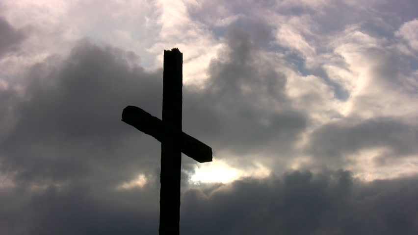 A large cross silhouetted against storm clouds at sunset. - HD stock footage clip