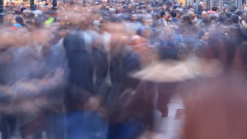 Crowd timelapse background. City pedestrian traffic shot on a busy Barcelona shopping street. Slow speed shot with a lot of people running by. Fast paced life concept.