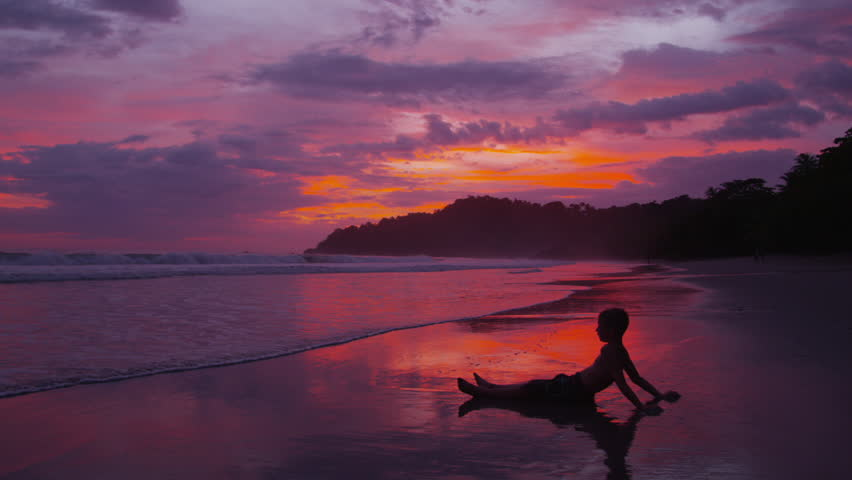 Cinemagraph - Young boy sitting on beach at sunset, Costa Rica. Looping Motion Photo.