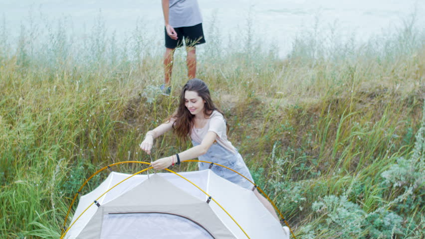 Young, attractive, sporty, smiling boy takes selfie on the background of his girlfriend, and tent. girl picks up the food and smiles when her boyfriend makes the photo. Teens have a good time together