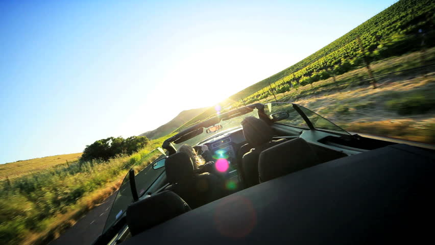 Visitors driving an open top car through the wine region of Napa Valley as the sun sets