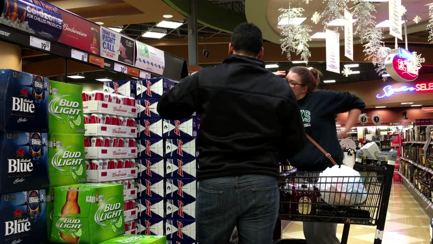 Coquitlam, BC, Canada - November 20, 2015 : Couple buying Budweiser beer inside BC liquor store with 4k resolution