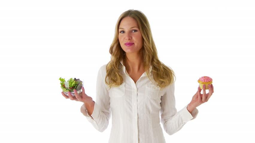 Woman deciding between salad and cupcake - HD stock footage clip