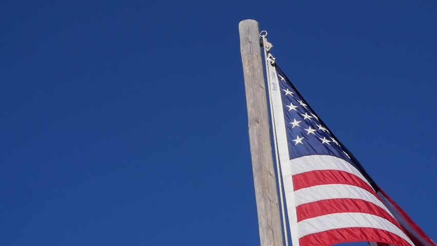 A slow motion shot of a beautiful American flag blows in a strong wind against a blue sky backdrop - HD stock video clip