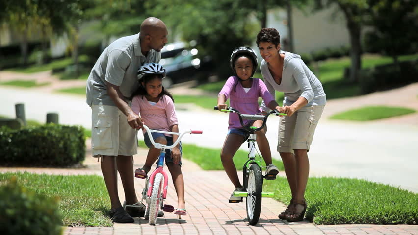 Little african american girls being helped to ride a bicycle by her parents - HD stock footage clip